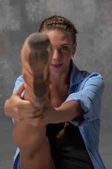 Młoda piękna tancerka w nowoczesnym stylu w niebieskiej koszuli, pozowanie na szarym tle studio. pointe ballerina w centrum uwagi