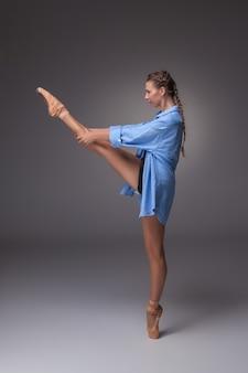 Młoda piękna tancerka w nowoczesnym stylu w niebieskiej koszuli, pozowanie na szarym tle studio