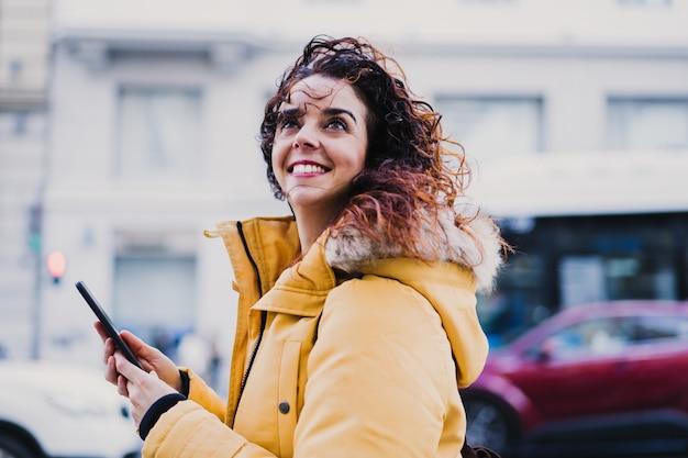 Młoda piękna turystyczna kobieta używa telefon komórkowego outdoors w ulicie. szczęśliwa uśmiechnięta kobieta koncepcja stylu życia i podróży