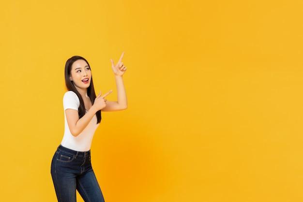 Młoda piękna uśmiechnięta azjatycka kobieta wskazuje up z jej dwoma palcami