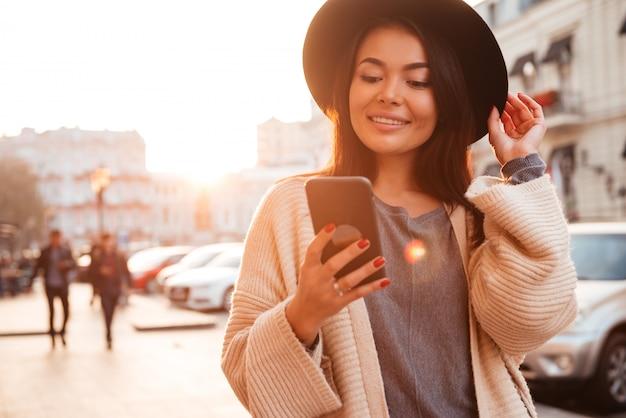 Młoda piękna uśmiechnięta azjatykcia kobieta dotyka jej kapelusz podczas gdy sprawdzać wiadomość na smartphone w miasto ulicie