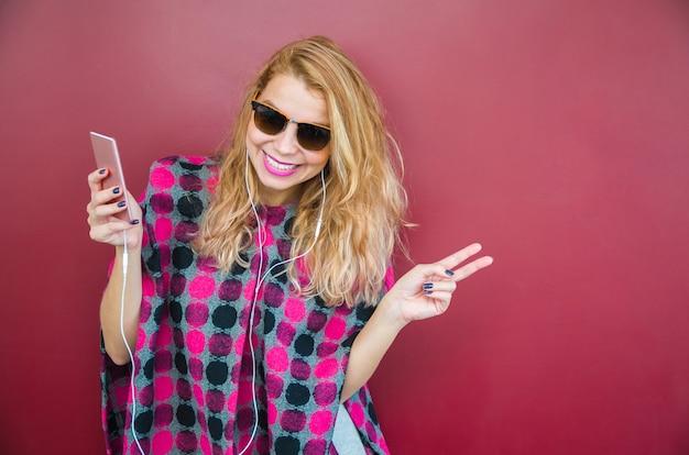 Młoda piękna uśmiechnięta blondynka ze słuchawkami, słuchanie muzyki i taniec.