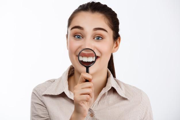 Młoda piękna uśmiechnięta brunetki dziewczyna pokazuje zęby przez magnifier nad biel ścianą.