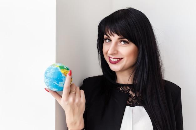 Młoda piękna uśmiechnięta brunetki kobieta trzyma kulę ziemską planety ziemia.