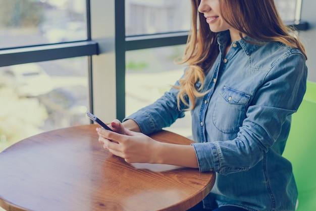 Młoda piękna uśmiechnięta dziewczyna ubrana w koszulę dżinsy, siedząc w kawiarni. otrzymuje wiadomości od swojego chłopaka. czyta najnowsze wiadomości w internecie. zbliżenie, przycięte zdjęcie