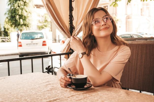 Młoda piękna uśmiechnięta hipster dziewczyna w modne letnie ubrania. beztroski kobieta siedzi w kawiarni na tarasie werandy i pije kawę. pozytywny model zabawy i marzeń