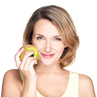 Młoda piękna uśmiechnięta kobieta dotyka jabłka w twarz na białym tle.