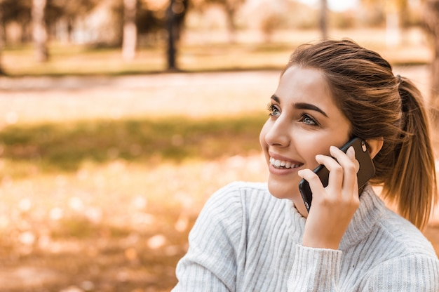 Młoda piękna uśmiechnięta kobieta opowiada na telefonie komórkowym w parku.