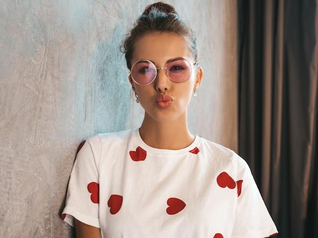 Młoda piękna uśmiechnięta kobieta patrzeje kamerę modna dziewczyna w przypadkowej lato białej sukni i okularach przeciwsłonecznych robi kaczki twarzy