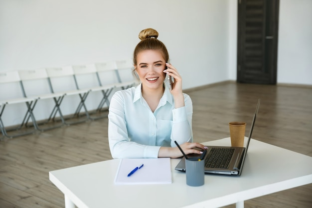 Młoda piękna uśmiechnięta kobieta pracuje w nowoczesnym biurze z laptopem. koncepcja sukcesu. konferencja online