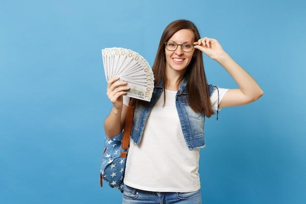 Młoda piękna uśmiechnięta kobieta studentka z plecakiem trzymając rękę na okularach trzymając pakiet wiele dolarów, pieniądze w gotówce na białym tle na niebieskim tle. edukacja w koncepcji liceum uniwersyteckiego.