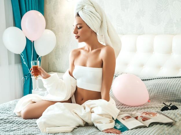 Młoda piękna uśmiechnięta kobieta w białej bieliźnie i ręczniku na głowie