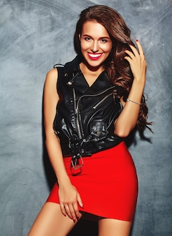 Młoda piękna uśmiechnięta kobieta w modnej letniej czerwonej spódnicy i czarnej skórzanej kurtce.