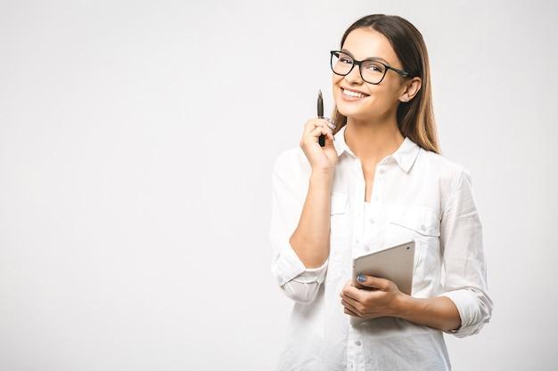 Młoda piękna uśmiechnięta kobieta w okularach trzymając pióro