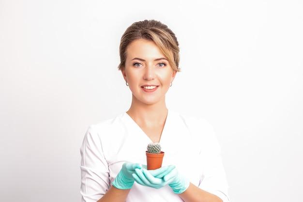 Młoda piękna uśmiechnięta kosmetyczka trzyma małego kaktusa w doniczce