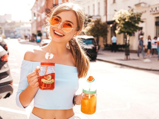 Młoda piękna uśmiechnięta modniś kobieta w okularach przeciwsłonecznych.