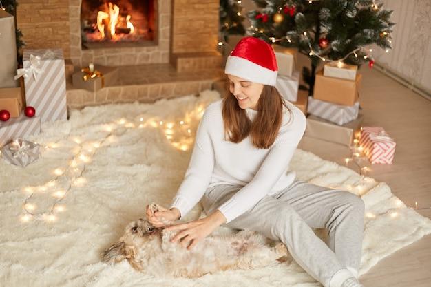 Młoda piękna uśmiechnięta szczęśliwa kobieta bawi się z psem wokół choinki i kominka, siedząc na dywanie ozdobionym światłami, kaukaska dama ze swoim pekińczykiem w domu.
