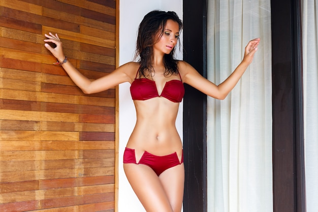 Młoda piękna uwodzicielska kobieta o idealnym ciele, pozująca w seksownym bikini w luksusowej willi, zrelaksowana na wakacjach, ma mokre włosy i jasny makijaż.