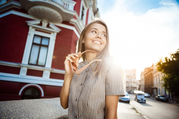 Młoda piękna wesoła kobieta w okularach przeciwsłonecznych spacerując po mieście, uśmiechając się.