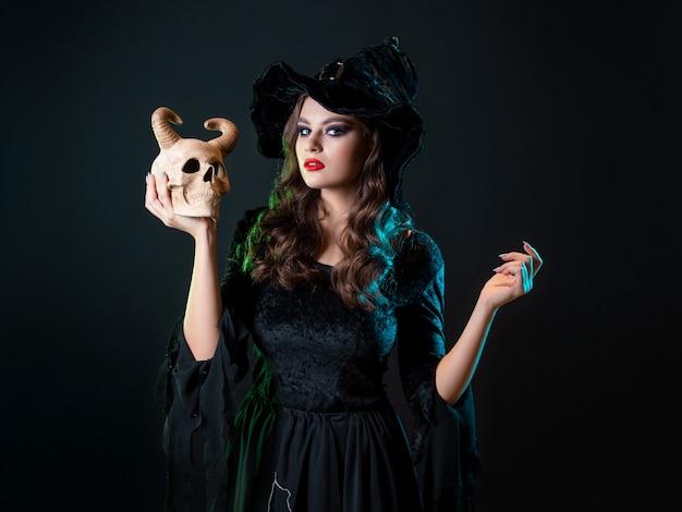 Młoda piękna wiedźma w stożkowatym kapeluszu trzyma w rękach czaszkę diabła