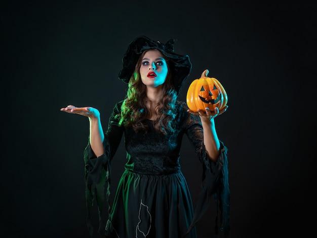 Młoda piękna wiedźma w stożkowatym kapeluszu trzyma w rękach halloweenową dynię