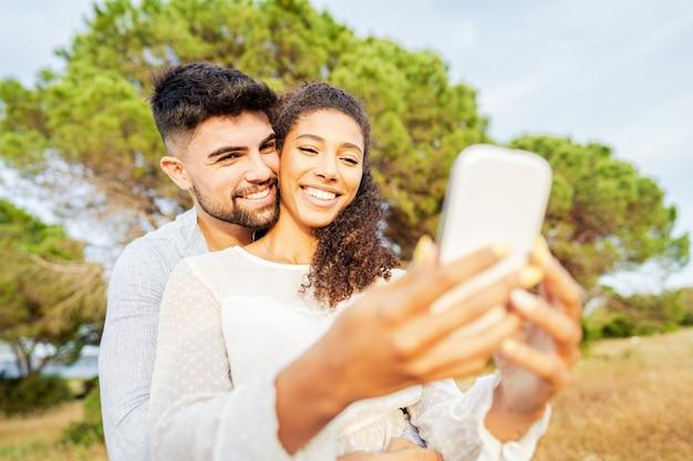 Młoda piękna wielorasowa para zakochanych przy selfie w przyrodzie, ciesząc się wakacyjnymi chwilami, udostępniając zdjęcia na portalach społecznościowych. nowe normalne uzależnienie od technologii z powodu połączeń mobilnych z internetem wi-fi
