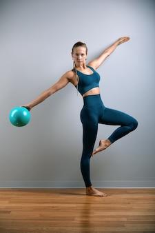Młoda, piękna, wysportowana dziewczyna robi ćwiczenia na fitball na siłowni