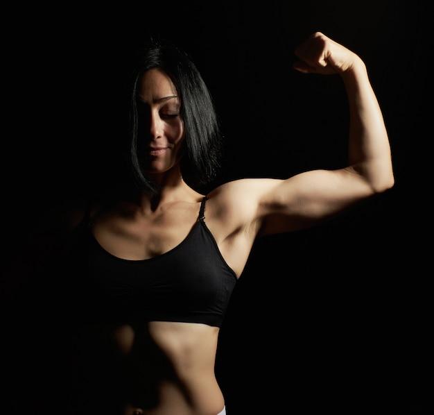 Młoda piękna wysportowana dziewczyna uniosła i pochyliła rękę, demonstrując biceps