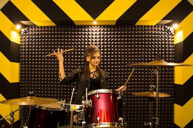 Młoda piękna wytatuowana dziewczyna w skórzanej kurtce gra na perkusji w studio nagrań na jasnym czarno-żółtym pasie