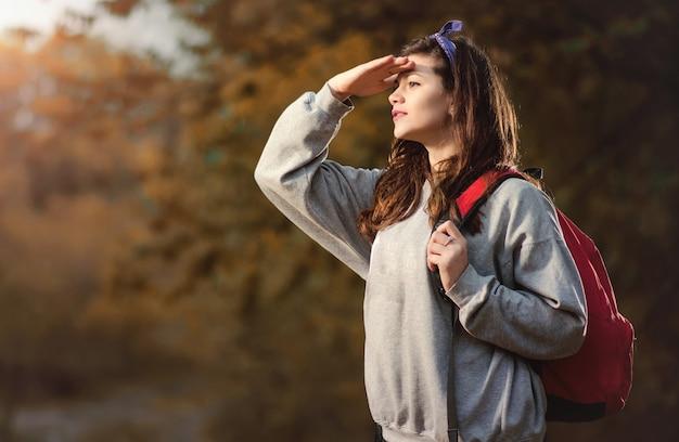 Młoda piękna z plecakiem na ramionach, zagubiona w nocnym lesie. jesienny wieczór