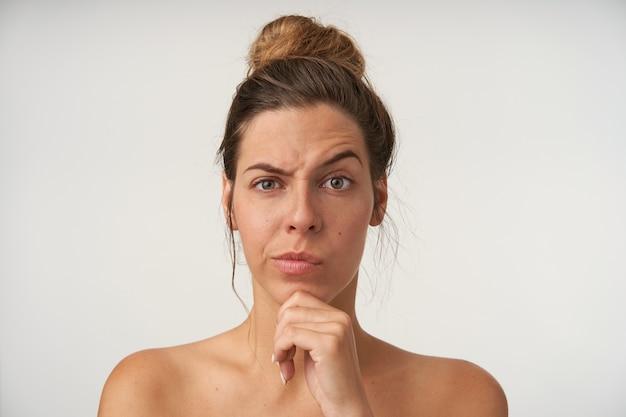 Młoda piękna zamyślona kobieta pozuje z przypadkową fryzurą, marszczy brwi, unosi brwi i trzyma dłonią jej brodę