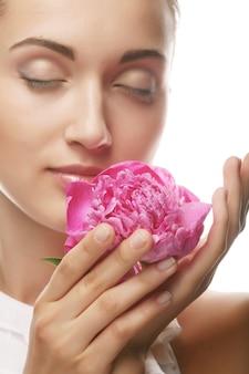 Młoda piękna zdrowa dziewczyna z różowym kwiatem na białym tle
