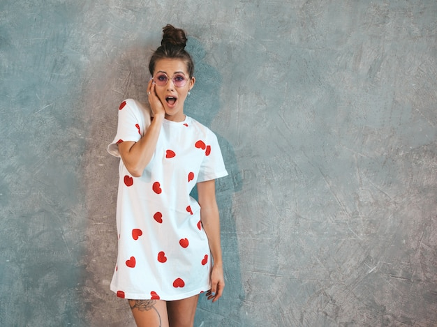 Młoda piękna zdziwiona kobieta patrzeje z rękami blisko usta. modna dziewczyna w białej, swobodnej letniej sukience.