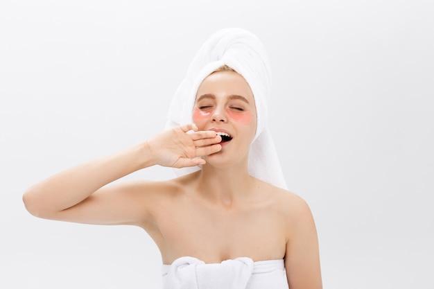 Młoda piękna ziewająca kobieta z kolagenów ochraniaczami pod jej oczami na lekkim tle. spa, pielęgnacja skóry oczu.