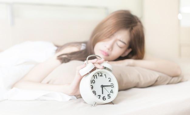 Młoda piękna zmęczona i leniwa kobieta próbuje się obudzić i wyłączyć budzik