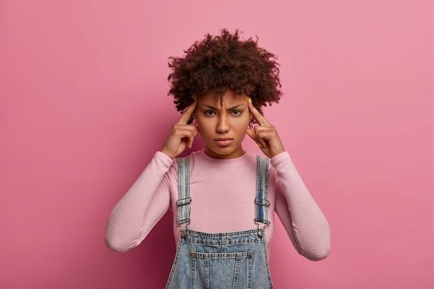 Młoda piękna zmęczona kobieta cierpi na migrenę lub ból głowy, dotyka skroni i wygląda intensywnie, prosi o środki przeciwbólowe, nosi dżinsową sarafan, stoi na tle różowej pastelowej ściany. negatywne uczucia