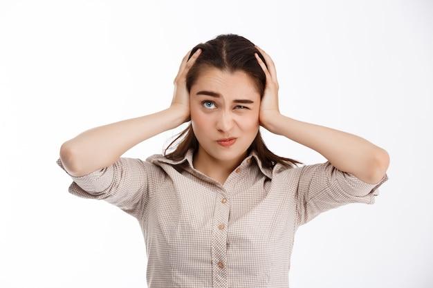 Młoda piękna zmieszana szalona brunetka businessgirl trzymając mocno głowę patrząc na białej ścianie