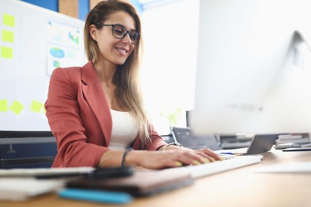 Młoda piękno kobieta używa komputer osobistego na miejsce pracy portrecie.