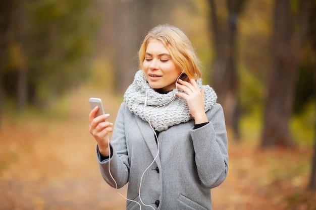 Młoda piękno kobiety słuchająca muzyka w jesień lesie