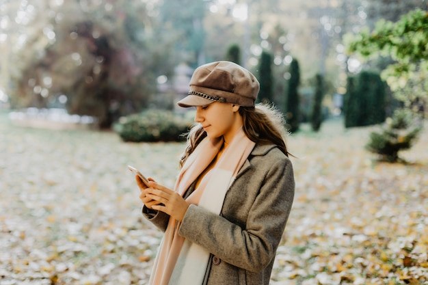 Młoda piękno kobiety writing wiadomość na telefonie komórkowym w jesień parku