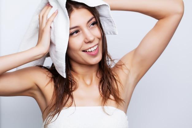 Młoda piękność wyciera włosy miękkim ręcznikiem po zabiegach pielęgnacyjnych.
