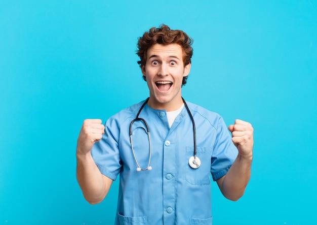 Młoda pielęgniarka czuje się zszokowana, podekscytowana i szczęśliwa, śmieje się i świętuje sukces, mówiąc wow!