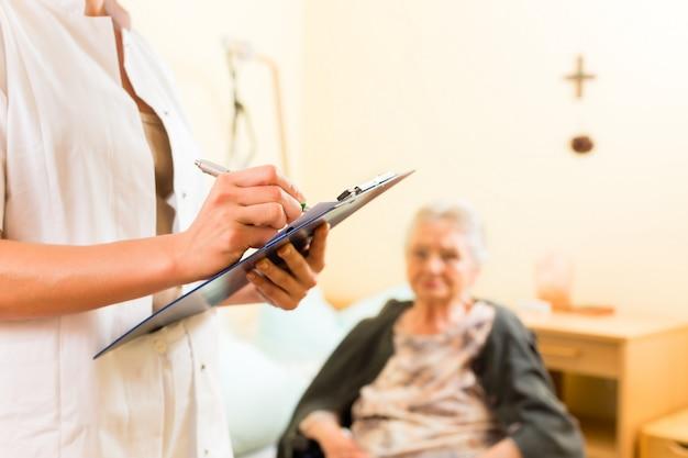 Młoda pielęgniarka i kobieta starszy w domu opieki