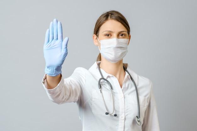 Młoda pielęgniarka lub lekarz kobieta ubrana w medyczną maskę na twarz i jednorazowe rękawiczki pokazujące gest stopu na białym tle na szarej ścianie