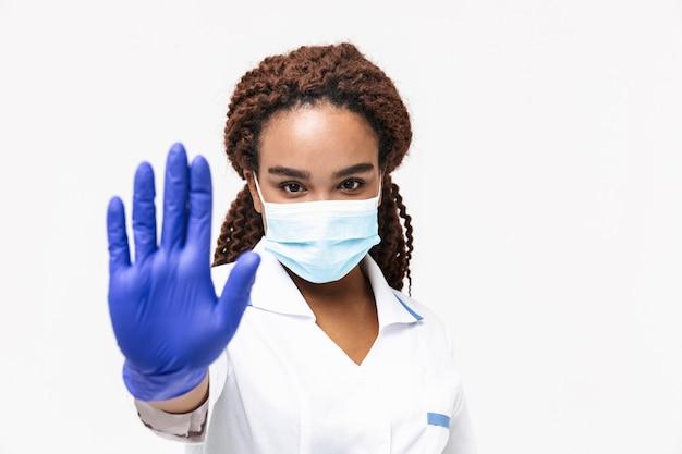 Młoda pielęgniarka nosząca medyczną maskę na twarz i jednorazowe rękawiczki pokazujące gest zatrzymania na białym tle na białej ścianie
