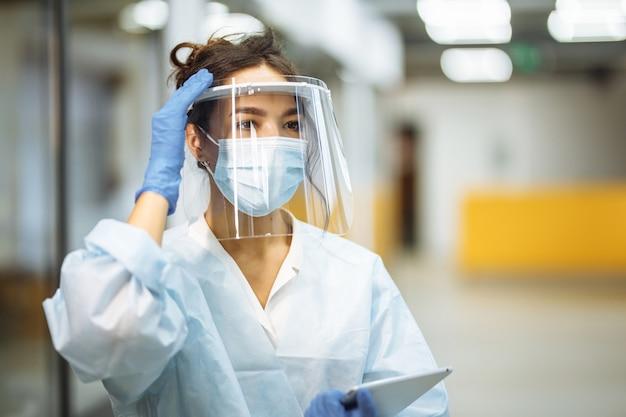 Młoda pielęgniarka poprawia osłonę twarzy na korytarzu szpitalnym podczas pandemii koronawirusa. portret profesjonalnego pracownika medycznego w miejscu pracy. koncepcja opieki zdrowotnej, medycyny i bezpieczeństwa.