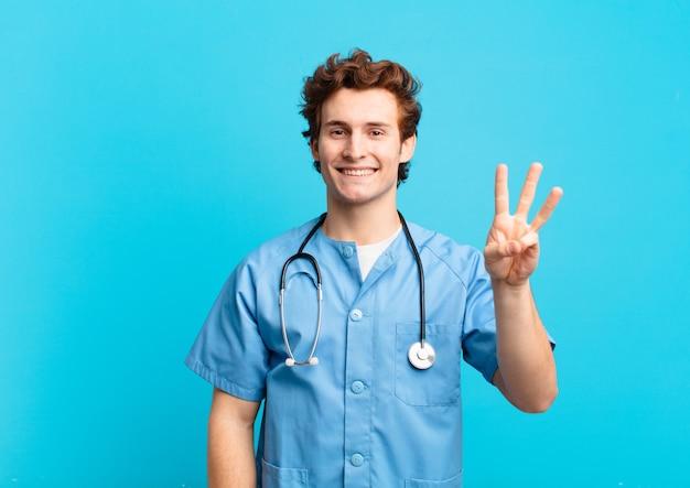 Młoda pielęgniarka uśmiecha się i wygląda przyjaźnie, pokazując numer trzy lub trzeci z ręką do przodu, odliczając