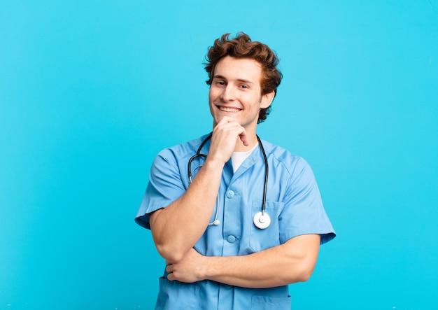 Młoda pielęgniarka uśmiecha się ze szczęśliwym, pewnym siebie wyrazem twarzy z ręką na brodzie, zastanawiając się i patrząc w bok