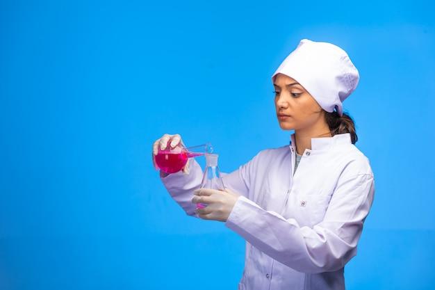 Młoda pielęgniarka w białym fartuchu przeprowadza test na wirusa.