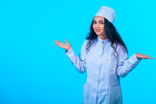 Młoda pielęgniarka w izolowanym mundurze wygląda pozytywnie